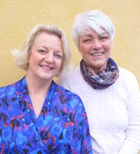 Två kvinnor ler mot kameran