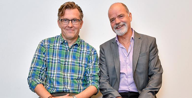 Håkan och Lasse sitter bredvid varandra, tittar och ler in i kameran